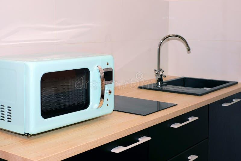 Νεροχύτης κουζινών και κρουνός στην κουζίνα σε ένα σύγχρονο διαμέρισμα Εσωτερικές συσκευές, φούρνος μικροκυμάτων και σόμπα επαγωγ στοκ εικόνες με δικαίωμα ελεύθερης χρήσης
