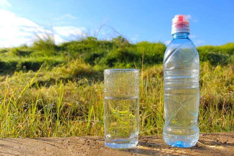 Νερό Κρύο μεταλλικό νερό σε μια κούπα γυαλιού και ένα πλαστικό μπουκάλι νερό στοκ εικόνα με δικαίωμα ελεύθερης χρήσης