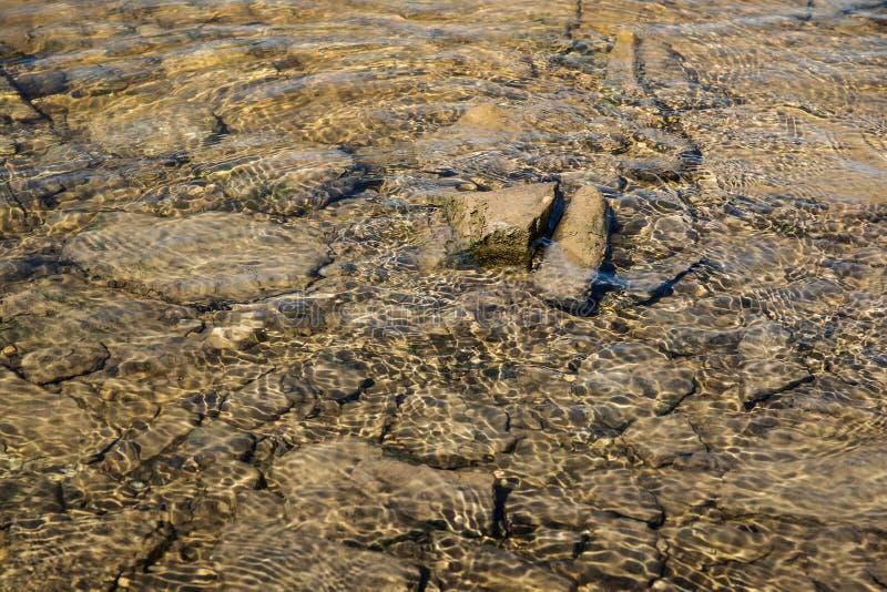 Νερό με τις ηλιαχτίδες και τις πέτρες στοκ εικόνα