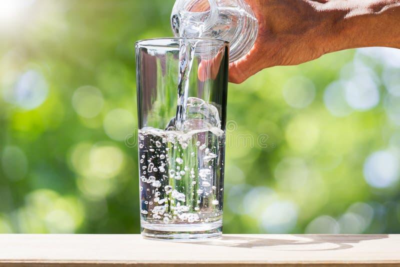 Νερό μπουκαλιών νερό κατανάλωσης εκμετάλλευσης χεριών ατόμων ` s και χύνοντας νερό στο γυαλί ξύλινο tabletop στο θολωμένο πράσινο στοκ εικόνες