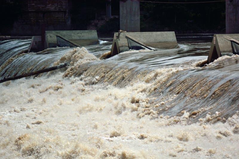 Νερό ποταμού που ρέει γρήγορα πέρα από ένα φράγμα υπερχείλισης στοκ φωτογραφίες