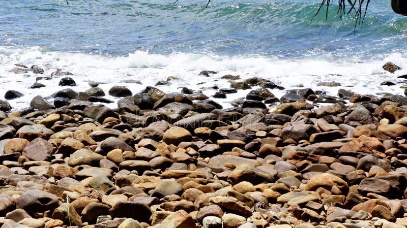 Νερό που περιτυλίγει την παραλία χαλικιών στοκ εικόνα