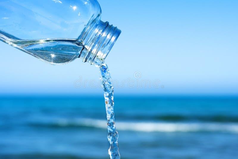 Νερό που ρέει έξω ενός επαναχρησιμοποιήσιμου μπουκαλιού γυαλιού στοκ εικόνα