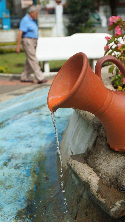 Νερό που ρέει από το αγγείο στην πηγή του πάρκου Palomino Flores στο στο κέντρο της πόλης της πόλης Banos στοκ εικόνες