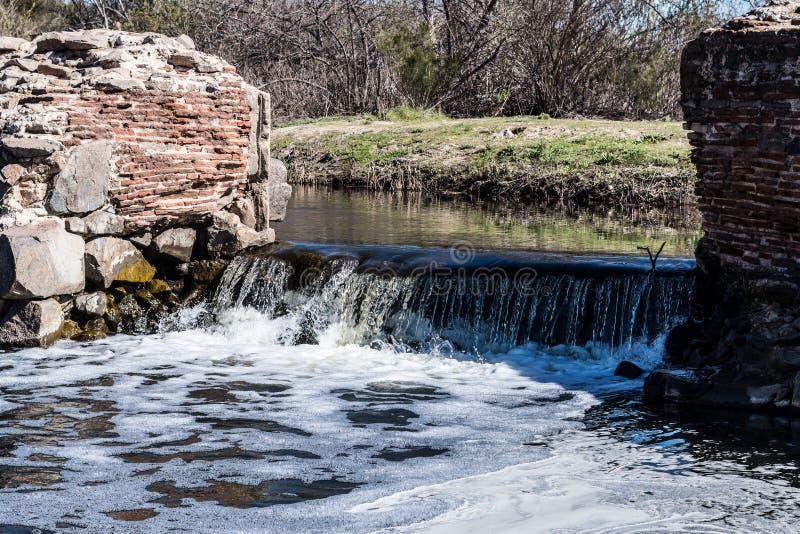 Νερό που ρέει πέρα από τον καταρράκτη στο παλαιό φράγμα αποστολής στοκ φωτογραφίες