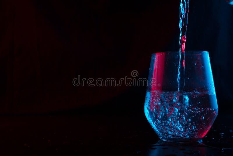 Νερό που τονίζεται στο μπλε και κόκκινο ράντισμα σε ένα γυαλί στοκ εικόνα