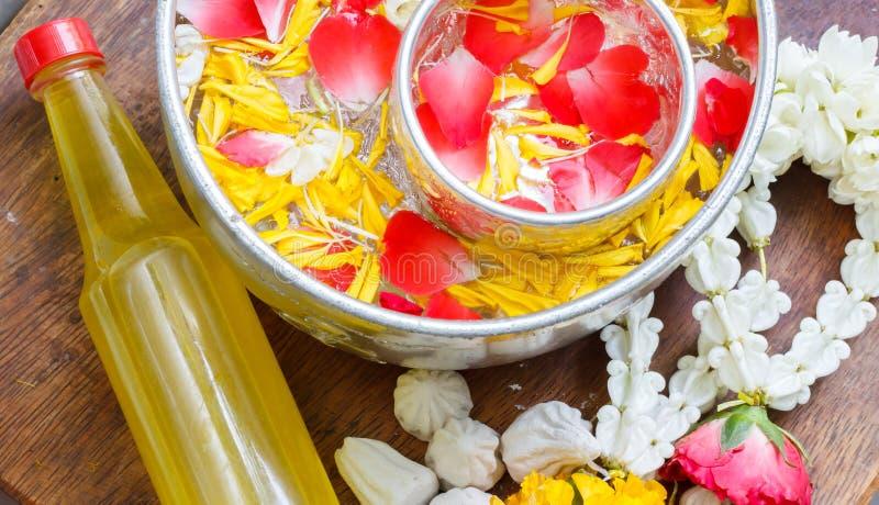 Νερό στο κύπελλο που αναμιγνύεται με το άρωμα και το ζωηρό corolla λουλουδιών, φεστιβάλ Songkran της Ταϊλάνδης στοκ εικόνες