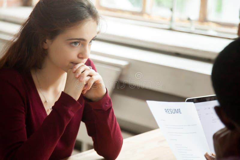 Νευρική ανησυχημένη γυναίκα υποψήφιος στη συνέντευξη εργασίας, εργοδότης που διαβάζεται στοκ φωτογραφία