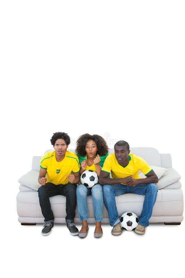 Νευρικοί βραζιλιάνοι οπαδοί ποδοσφαίρου σε κίτρινο στον καναπέ στοκ εικόνες