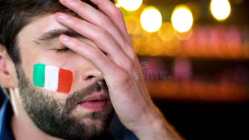 Νευρικός γενειοφόρος αρσενικός ανεμιστήρας με την ιταλική σημαία στο μάγουλο που κάνει facepalm, απώλεια ομάδων στοκ εικόνες