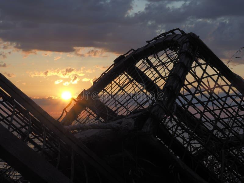 Νεφελώδες ηλιοβασίλεμα με τις παγίδες αστακών στη σκιαγραφία στοκ φωτογραφίες