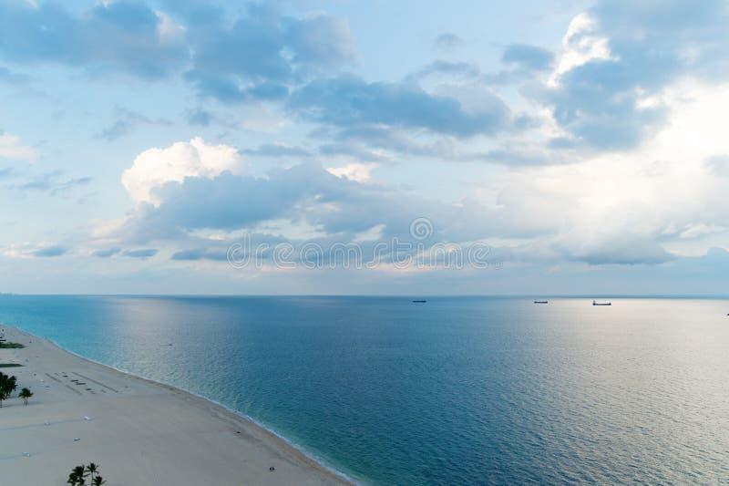 Νεφελώδης ημέρα στην παραλία Άσπρα σύννεφα επάνω από την ομαλή ωκεάνια επιφάνεια νερού Ήρεμη έννοια Ήρεμο βράδυ θάλασσας r στοκ εικόνες