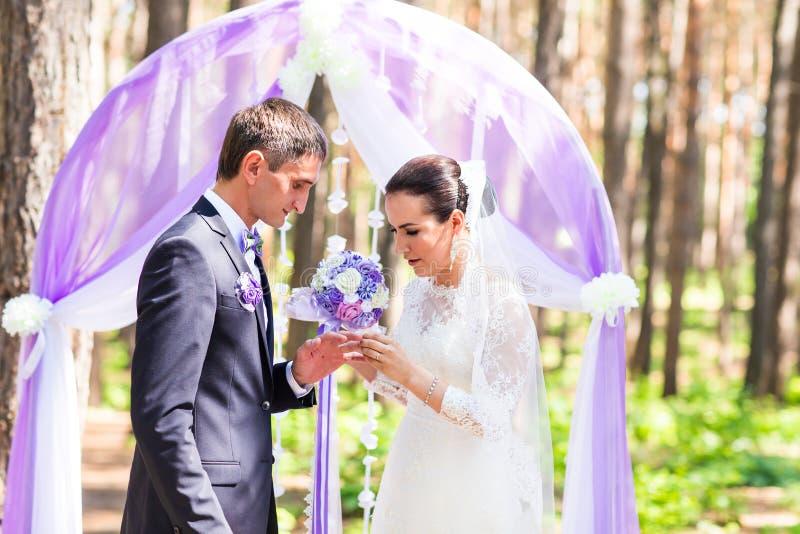 νεόνυμφος δάχτυλων νυφών που βάζει το γάμο δαχτυλιδιών s γάμος λουλουδιών τελετής νυφών στοκ φωτογραφίες με δικαίωμα ελεύθερης χρήσης