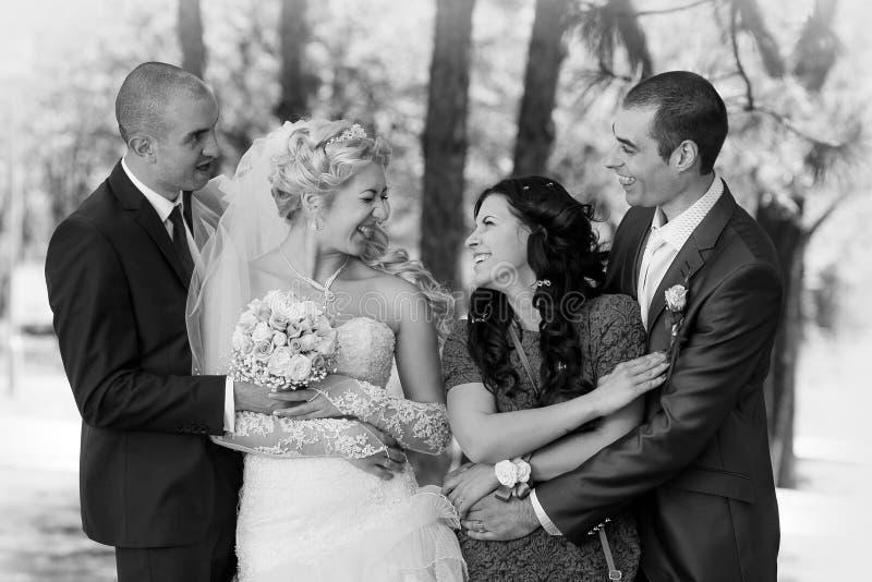 Νεόνυμφος, η νύφη και το καλύτερο άτομο με το μάρτυρα στο πάρκο στοκ εικόνα