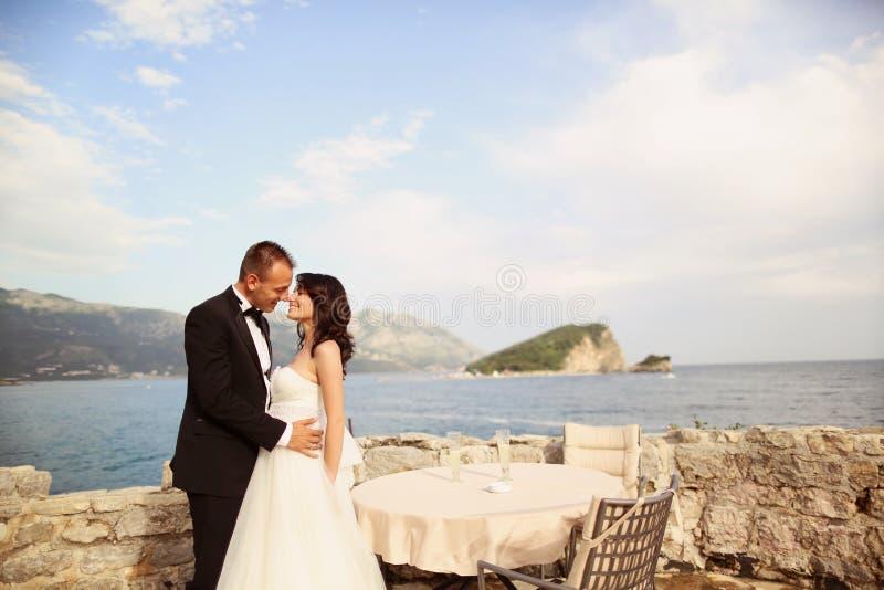 Νεόνυμφος και νύφη κοντά στη θάλασσα στοκ εικόνες