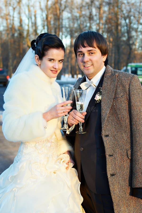 Νεόνυμφος και νύφη με τα ποτήρια της σαμπάνιας στοκ φωτογραφίες