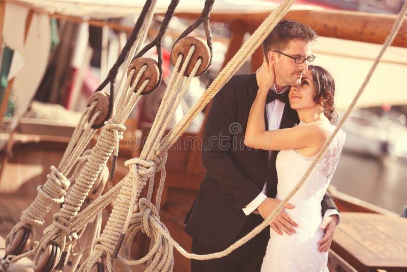 Νεόνυμφος και νύφη σε ένα σκάφος με τις σειρές στοκ εικόνες