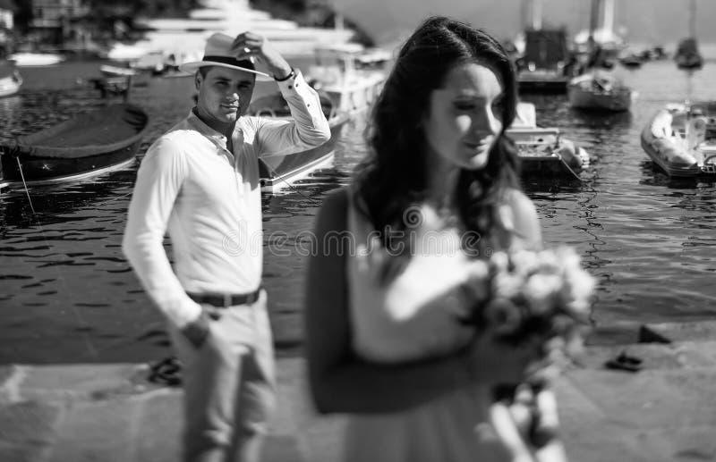 Νεόνυμφος και νύφη στο άσπρο φόρεμα που αγκαλιάζουν το υπόβαθρο θάλασσας στοκ φωτογραφίες