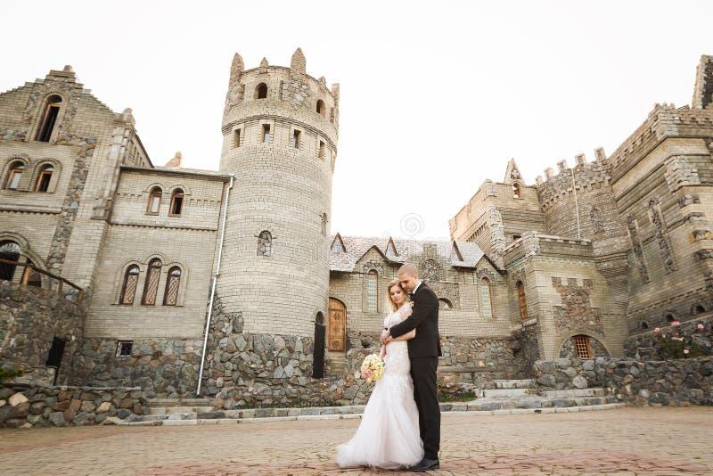 Νεόνυμφος που αγκαλιάζει τη νύφη στο υπόβαθρο του παλαιού κτηρίου στοκ φωτογραφία