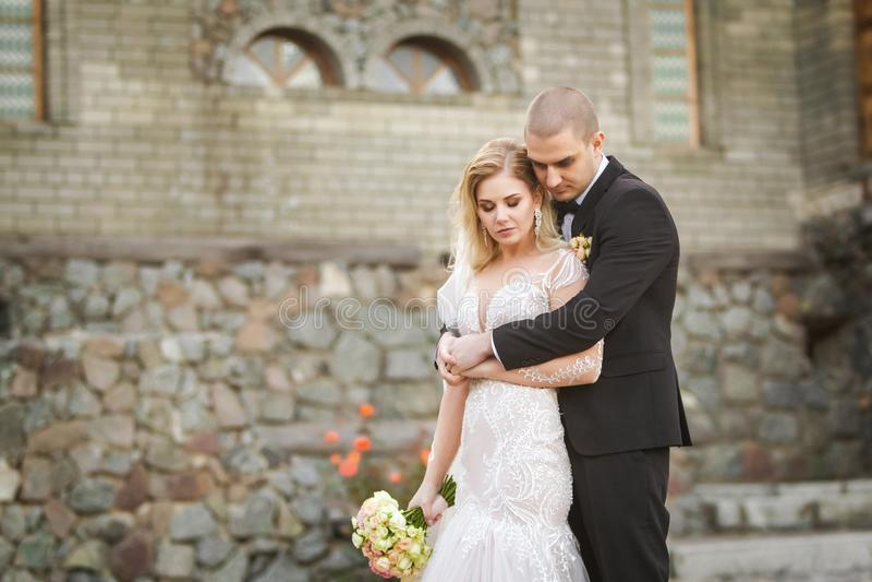 Νεόνυμφος που αγκαλιάζει τη νύφη στο υπόβαθρο του παλαιού κτηρίου στοκ φωτογραφία με δικαίωμα ελεύθερης χρήσης