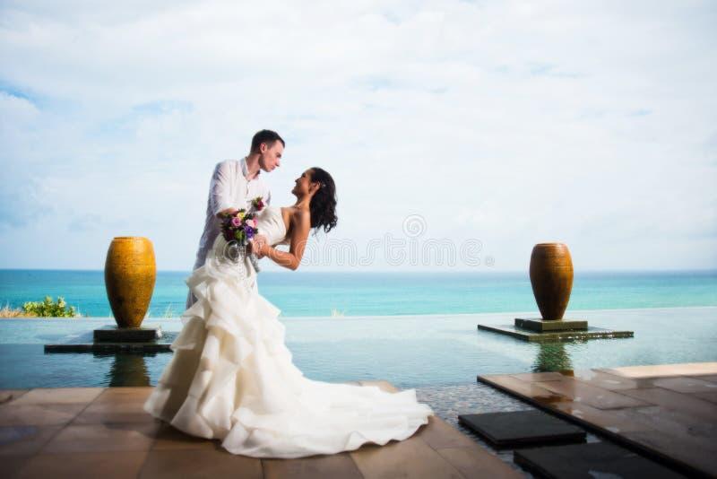 Νεόνυμφος που αγκαλιάζει τη νύφη στο υπόβαθρο του ωκεανού Ρομαντική γαμήλια φωτογραφία στοκ φωτογραφία με δικαίωμα ελεύθερης χρήσης