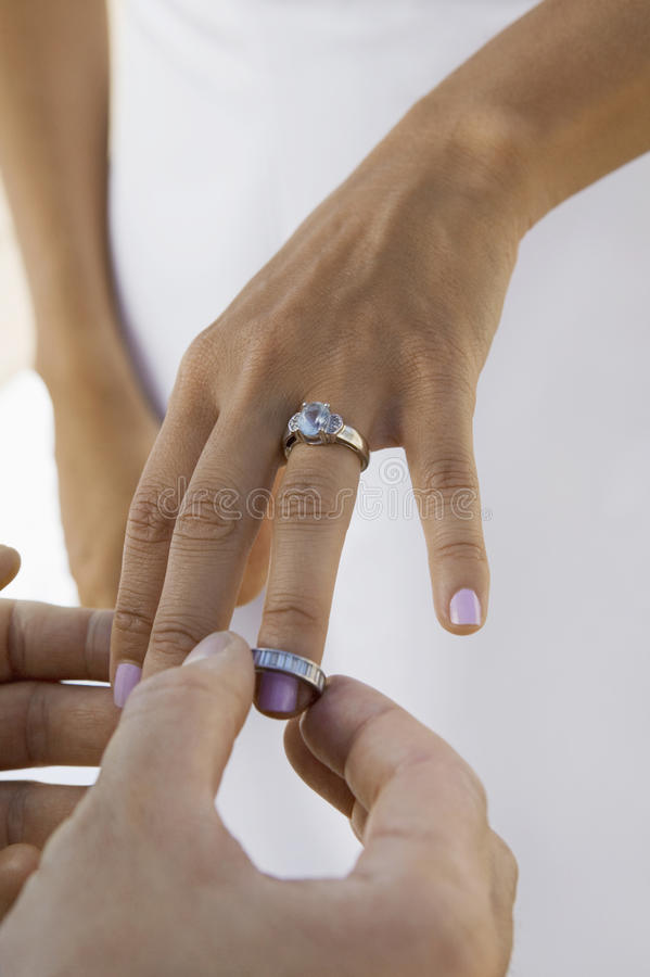 Νεόνυμφος που βάζει το γαμήλιο δαχτυλίδι στο δάχτυλο νυφών (κινηματογράφηση σε πρώτο πλάνο) στοκ εικόνα με δικαίωμα ελεύθερης χρήσης