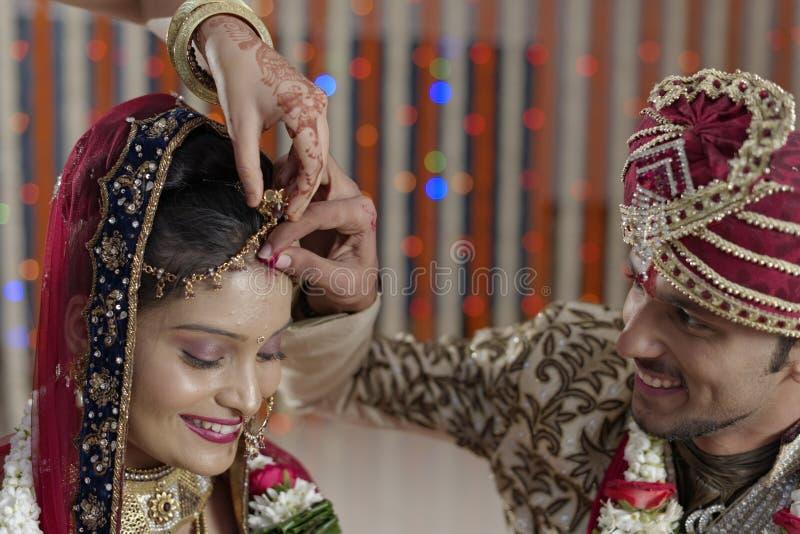 Νεόνυμφος που βάζει Sindoor στο μέτωπο της νύφης στον ινδικό ινδό γάμο. στοκ φωτογραφία με δικαίωμα ελεύθερης χρήσης