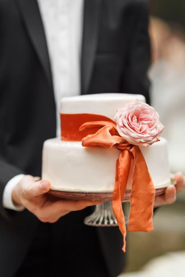 Νεόνυμφος που κρατά ένα γαμήλιο κέικ στοκ εικόνες