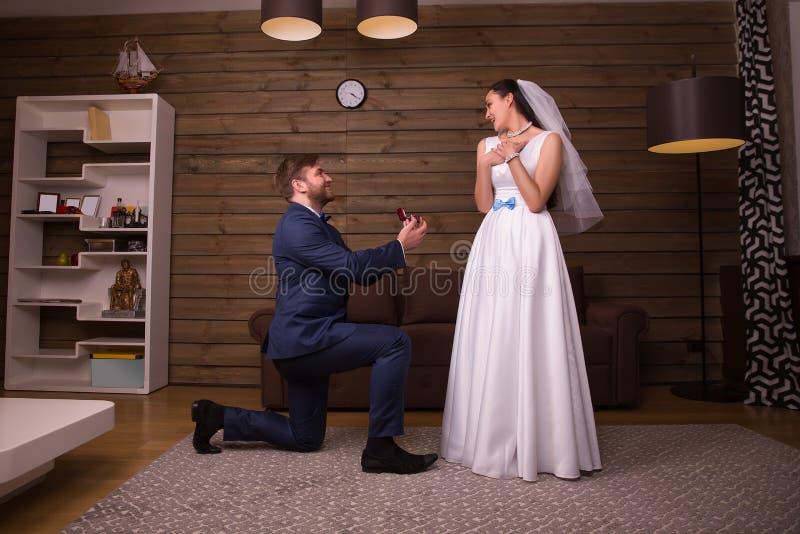 Νεόνυμφος που στέκεται στα γόνατά του ενάντια στην ευτυχή νύφη στοκ φωτογραφίες
