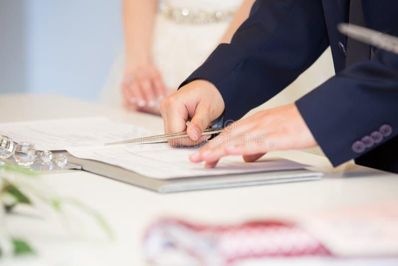 Νεόνυμφος που υπογράφει τη γαμήλια άδεια στοκ εικόνες