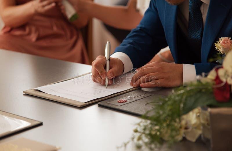 Νεόνυμφος που υπογράφει το πιστοποιητικό γάμου στοκ εικόνες