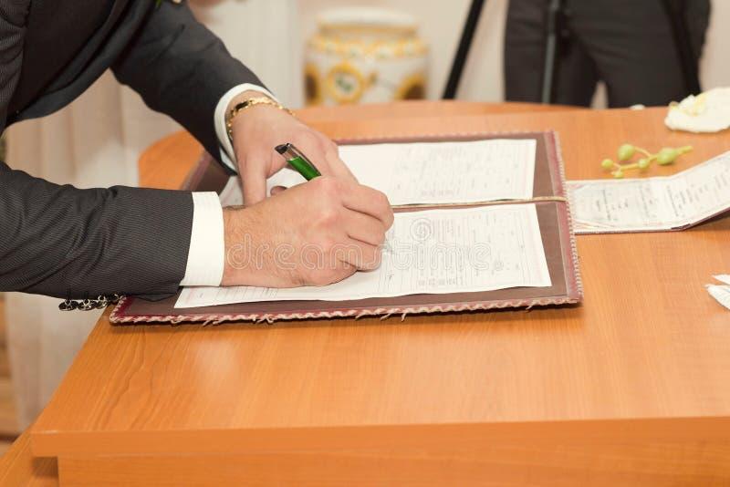 Νεόνυμφος που υπογράφει το πιστοποιητικό γάμου στοκ φωτογραφία