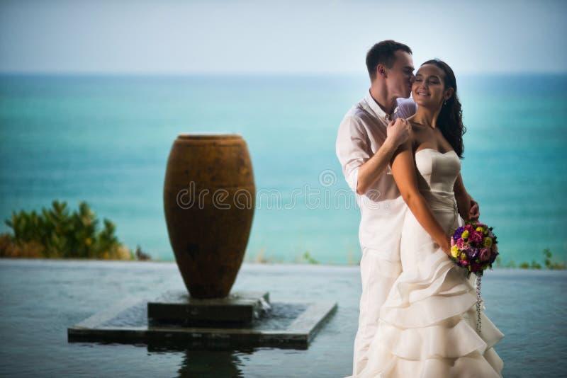 Νεόνυμφος που φιλά την όμορφη νύφη στο ωκεάνιο υπόβαθρο στοκ φωτογραφία με δικαίωμα ελεύθερης χρήσης