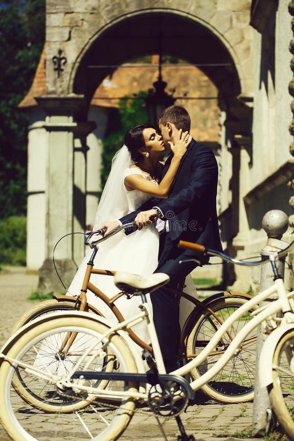 Νεόνυμφος φιλιών νυφών στο ποδήλατο στοκ εικόνες