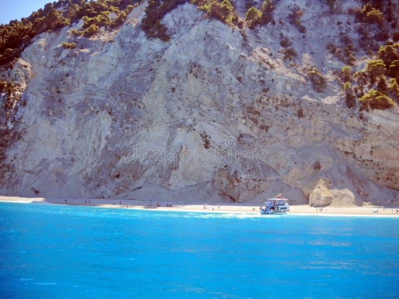 Νησί και τυρκουάζ θάλασσα με το μικρό ταχύπλοο σκάφος και τουρίστες στην παραλία στοκ εικόνα με δικαίωμα ελεύθερης χρήσης