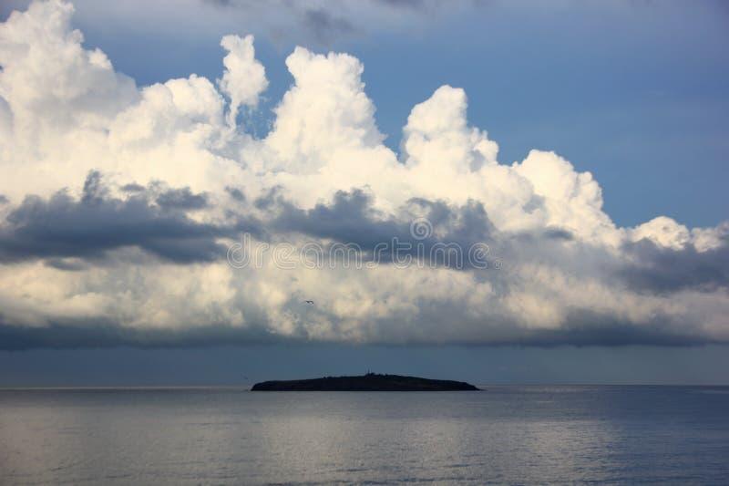 Νησί στη Μαύρη Θάλασσα πέρα από την οποία ο μαζευμένος σωρείτης καλύπτει στοκ εικόνα με δικαίωμα ελεύθερης χρήσης
