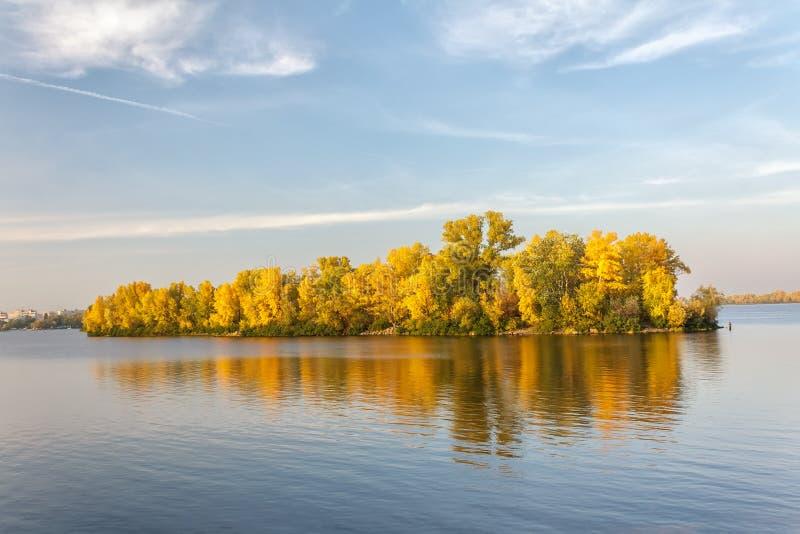 Νησί φθινοπώρου και η αντανάκλασή του στο μπλε νερό στοκ φωτογραφίες