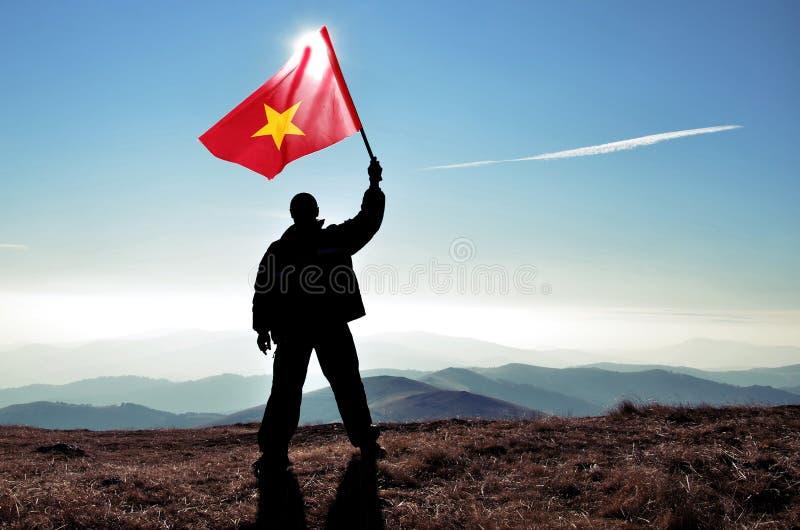 Νικητής ατόμων που κυματίζει τη σημαία του Βιετνάμ πάνω από την αιχμή βουνών στοκ φωτογραφία