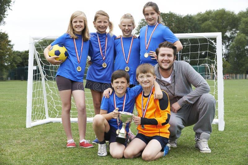 Νικηφορόρη ομάδα σχολικού ποδοσφαίρου με τα μετάλλια και το τρόπαιο στοκ εικόνα