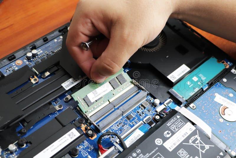 ΝΙΚΟΠΟΛΗ, ΟΥΚΡΑΝΙΑ - ΤΟΝ ΙΟΎΝΙΟ ΤΟΥ 2018: Ο τεχνικός κρατά το κατσαβίδι για την επισκευή του υπολογιστή, η έννοια του υλικού υπολ στοκ φωτογραφία