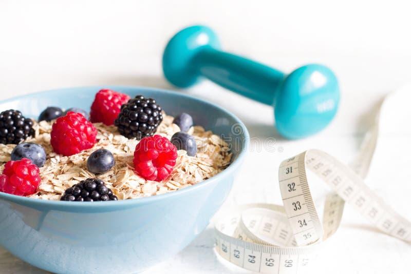 Νιφάδες βρωμών κουάκερ με έννοια αθλητικής την υγιή διατροφής μούρων και αλτήρων στοκ εικόνες