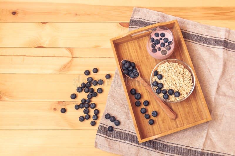 Νιφάδες βρωμών με τα βακκίνια στο γιαούρτι κύπελλων και βακκινίων στον ξύλινο πίνακα Έννοια των υγιών τροφίμων στοκ εικόνες