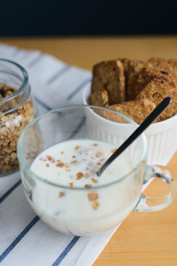 Νιφάδες γάλακτος και δημητριακών στο φλυτζάνι γυαλιού με το granola και τα wholegrain μπισκότα στοκ εικόνες με δικαίωμα ελεύθερης χρήσης