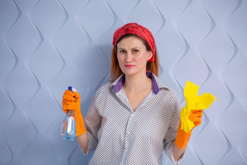 Νοικοκυρά γυναικών με να καθαρίσει τον ψεκασμό και το κουρέλι μπουκαλιών υπό εξέταση στο μπλε υπόβαθρο στοκ φωτογραφίες με δικαίωμα ελεύθερης χρήσης