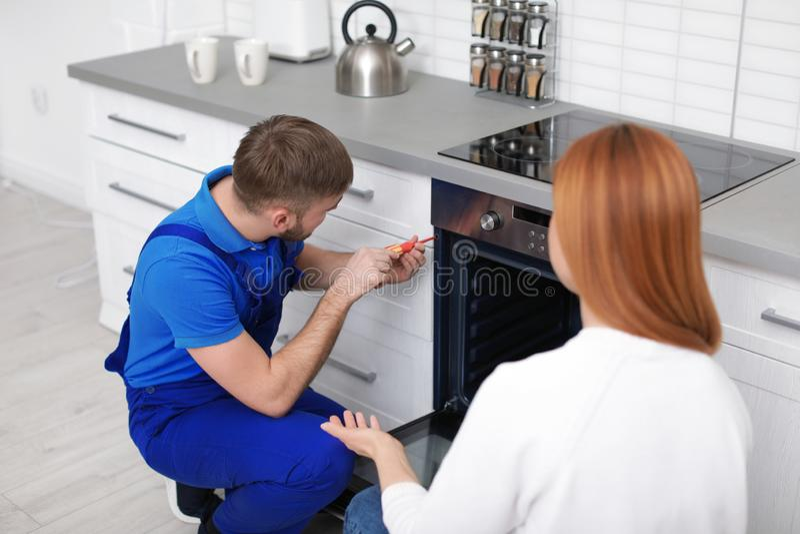 Νοικοκυρά με τον επισκευαστή κοντά στο σύγχρονο φούρνο στοκ φωτογραφίες με δικαίωμα ελεύθερης χρήσης