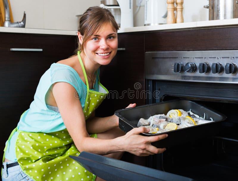 Νοικοκυρά που βάζει το δίσκο με τα ψάρια στο φούρνο στοκ εικόνες με δικαίωμα ελεύθερης χρήσης