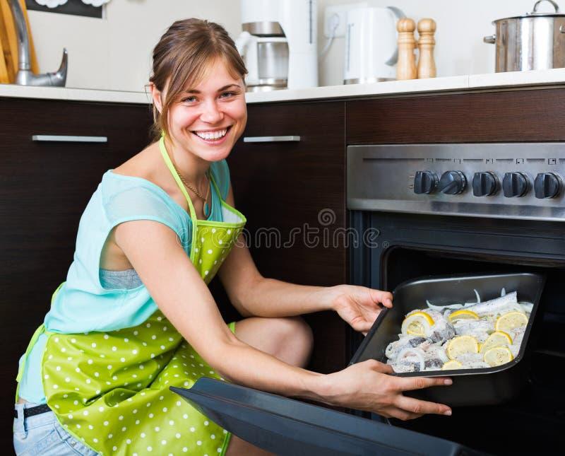 Νοικοκυρά που βάζει το δίσκο με τα ψάρια στο φούρνο στοκ εικόνες