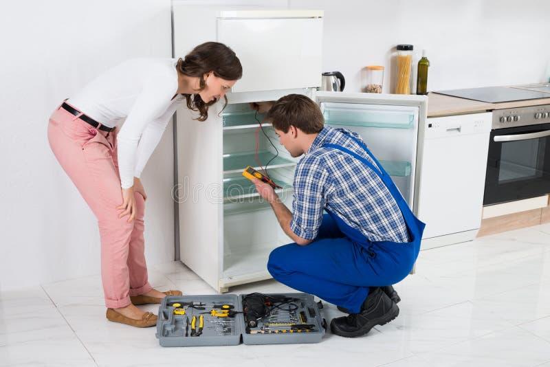 Νοικοκυρά που εξετάζει τον εργαζόμενο που επισκευάζει το ψυγείο στοκ εικόνες