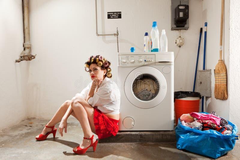 Νοικοκυρά που τρυπιέται στο πλυντήριο στοκ φωτογραφίες