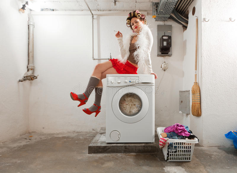 Νοικοκυρά που τρυπιέται στο πλυντήριο στοκ εικόνες